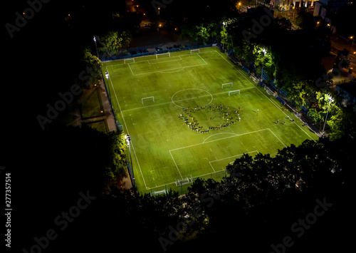 Aerial view of football pitch at night with amateur football players playing the Canvas Print