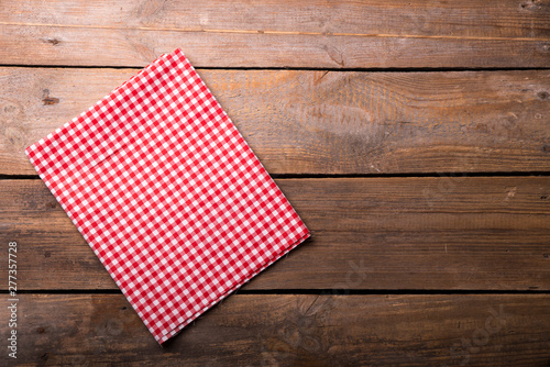 Fotografie, Obraz Empty wooden deck table and red checked tablecloth over mint wallpaper backgroun