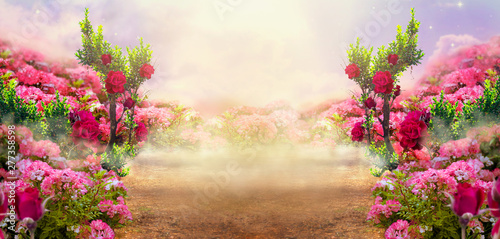 Fantasy summer panoramic photo background with rose field, trees and misty path leading to mysterious glade. Idyllic tranquil morning scene and empty copy space. Road goes across hills to fairytale.