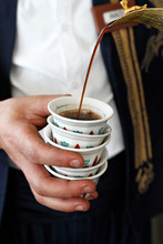 Man In Traditonal Clothes Pouring Coffee Into  Arabic Coffee Cups