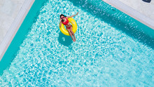 Aerial View Of Young Sexy Woman In Bikini Swimming On The Inflatable Big Yellow Ring In Pool