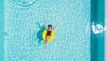 Vacation Concept. Top View Of Slim Young Woman In Bikini On The Yellow Air Inflatable Ring In The Swimming Pool.