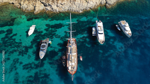 Aerial drone photo of luxury yachts docked in famous turquoise clear sea bay of Ornos, Mykonos island, Cyclades, Greece