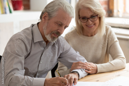 Fotomural  Happy older family couple husband and wife sign legal paper
