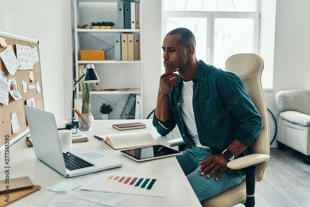 Fototapety, obrazy: So busy! Thoughtful young African man in shirt working while sitting in the office