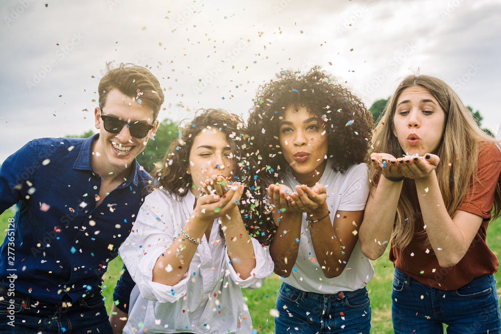 Fototapety, obrazy: Group of four friends having fun at the park blowing confetti - Millennials playing together at sunset