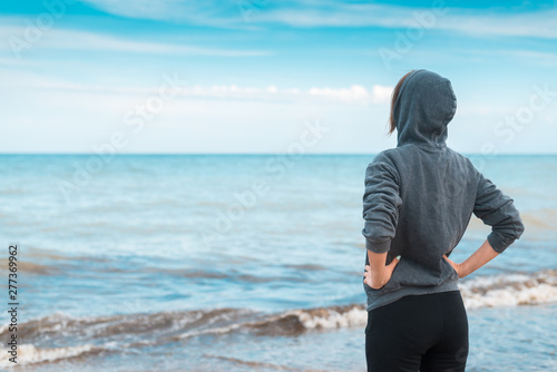 Montage in der Fensternische Licht blau A calm, confident woman in a hooded sweater stands on the seashore, the ocean. A middle aged woman holds her hands on her belt.