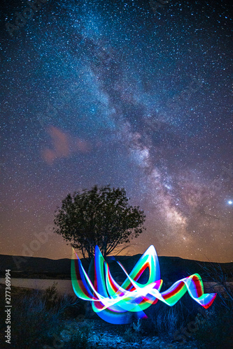Photo A young man playing with a light under the Milky Way in the swamp of Yesa and a beautiful tree