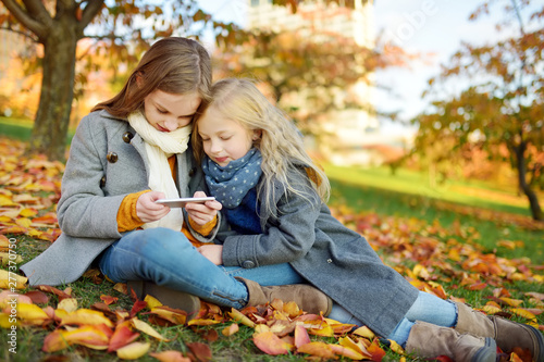 Obraz Two cute young sisters having fun on beautiful autumn day. Happy children playing in autumn park. Kids gathering yellow fall foliage. - fototapety do salonu