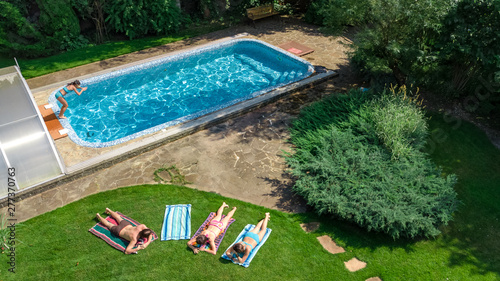 Photo  Happy family relaxing by swimming pool, aerial drone view from above of parents