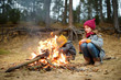 Two cute young girls sitting by a bonfire on cold autumn day. Children having fun at camp fire. Camping with kids in fall forest.