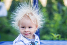 Cute Little Boy With Static Electricy Hair, Having His Funny Portrait Taken Outdoors