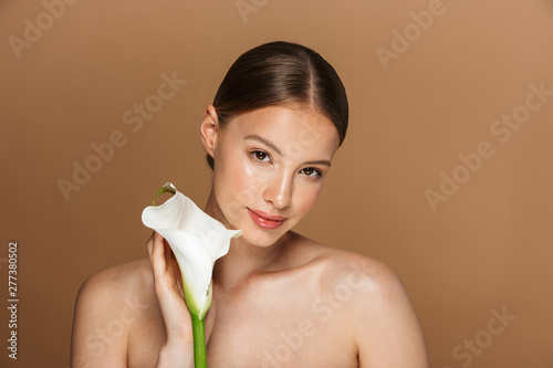 Image of beautiful half-naked woman looking at camera and holding white flower