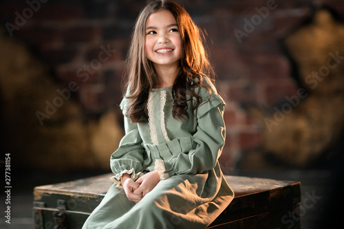 Poster Gypsy portrait of adorable smiling girl with long hair looking away while sitting on the wooden chest, studio shot