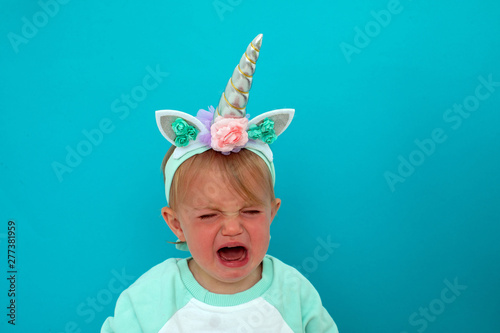 Leinwand Poster Upset baby with open mouth and eyes closed in unicorn costume crying in studio w