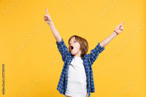 Obraz Fun cheerful happy little kid boy in blue shirt white t-shirt posing gesturing hands isolated on yellow wall background children studio portrait. People childhood lifestyle concept. Mock up copy space - fototapety do salonu