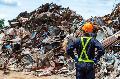 Valokuva  workers in landfill dumping, Garbage engineer, recycling, wearing a safety suit standing in the outdoor recycling center have a metal scrap pile in the background