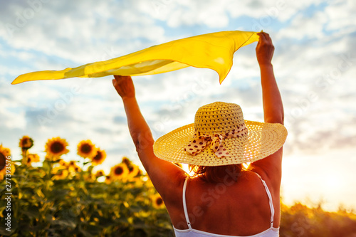 Photo Senior woman walking in blooming sunflower field raising hands with scarf and having fun