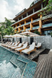 Modern architecture resort with pool, outdoor sun bathing chairs and umbrellas. Relax and hideaway place in Thailand.
