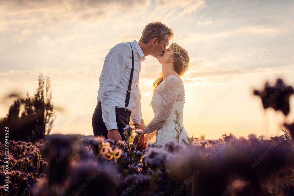 Fototapety, obrazy: Hochzeitspaar küsst sich zum Sonnenuntergang auf der Wiese nach der Hochzeit