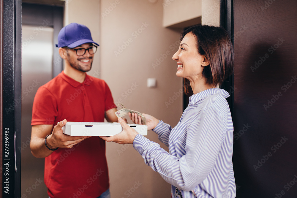 Fototapety, obrazy: Smiling young woman receiving pizza from delivery man at home.