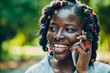 Portrait of an African beauty smiling young black woman in the park with a solar flare talking on the phone