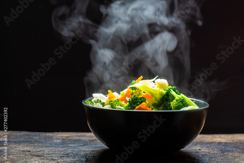 The steam from the vegetables carrot broccoli cauliflower on black bowl , a steaming Wallpaper Mural