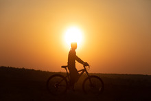 Happy Girl With A Bicycle On The Nature On The Background Of Bright Sunset And Yellow Sun