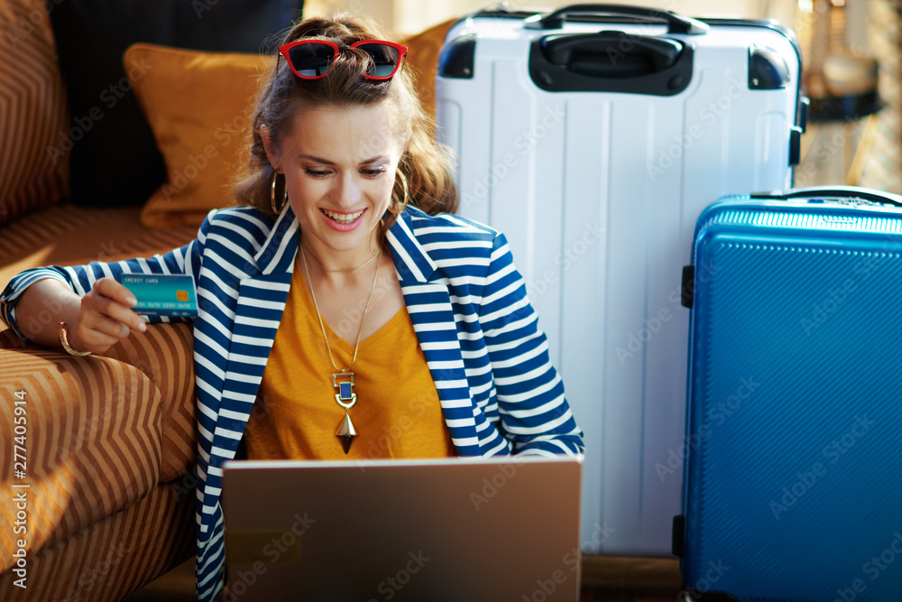 Fototapety, obrazy: smiling trendy woman with credit card booking tickets on laptop