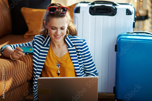 smiling trendy woman with credit card booking tickets on laptop