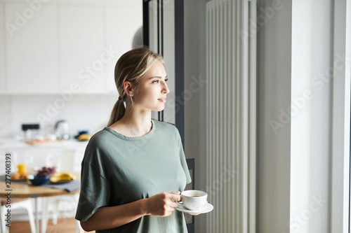 Poster Individuel Young casual woman with cup of coffee looking through window while staying at home on weekend