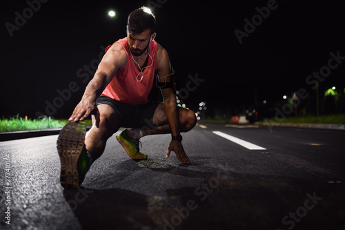 plakat Man preparing to run through the city at night, he stretching his leg muscles.