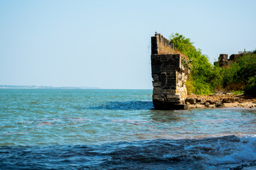 Moss and tree covered stone wall ending in ocean waves from diu fort in gujarat india