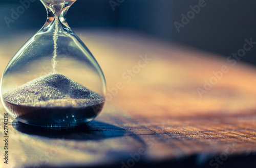 Fototapeta Sand running through the bulbs of an hourglass measuring the passing time in a countdown to a deadline with copy space