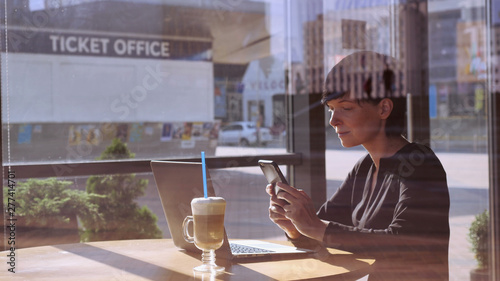 Young woman sitting in cafe near big windows chatting on smartphone looking on screen laptop Poster Mural XXL