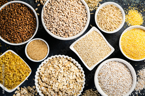 Fototapeta Selection of whole grains in white bowls - rice, oats, buckwheat, bulgur, porridge, barley, quinoa, amaranth on dark background obraz
