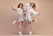 Fashion. Two Excited Woman Jumping Dance. Romantic Sister Friend Having Fun, Stylish Fashionable Summer Outfit. Carefree Beautiful Girl With Wavy Hair Dancing In Studio, Funny Concept