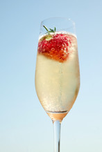 Glass Of Champagne With A Strawberry Fizzing In It