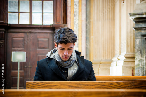 Valokuva Young man sitting and kneeling in church praying, on wood bench