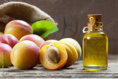 Leinwand Poster Glass bottle of Apricot seed kernel oil ( prunus armeniaca oleum ) with fresh ri