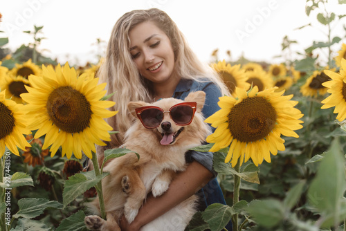 Fotografie, Obraz  A young woman and her small dog in a sunflower field