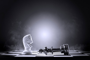 King chess piece defeating by knight chess piece
