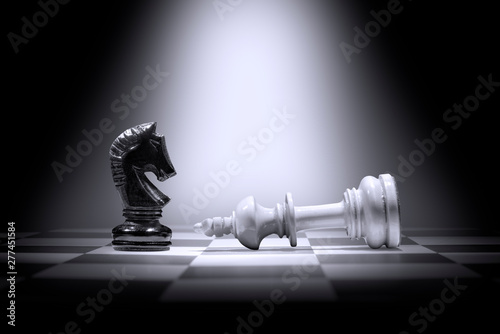 Fotografía White king chess piece defeating by black knight chess piece