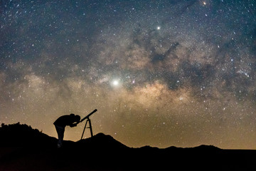 Silhouette of man watching star in telescope against  milky way galaxy with stars and space dust in the universe.