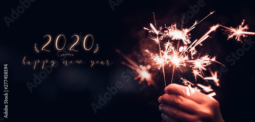 happy new year 2020 text with hand holding burning Sparkler firework blast with on a black bokeh background at night,holiday celebration event party,dark vintage tone Canvas Print