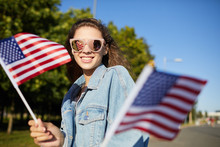 Portrait Of Jovial Student Girl In Pink Sunglasses And Denim Jacket Walking Over Street And Holding National Flags