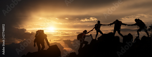 Fotografía Silhouette of Hikers climbing up mountain cliff