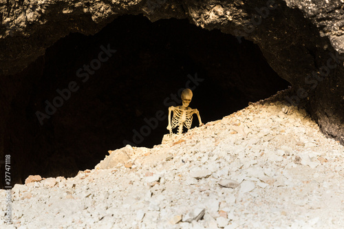 Skeleton in a dark cave in the ground crawling on rocks