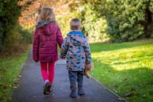 Siblings Walking Hand In Hand ...