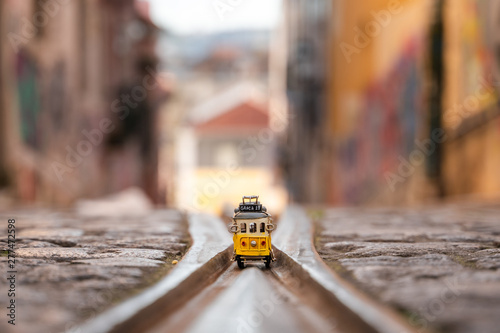 Fotografia, Obraz  Elevador da Bica: The famous yellow funicular railway line and a miniature train in Lisbon, Portugal